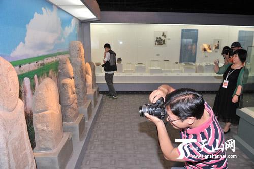 草原石人吸引着记者拍照