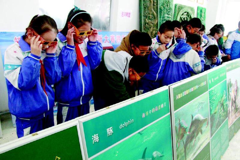 12月2日,几名中学生戴着立体眼镜观看三维科普宣传画.图片